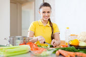 Woman in yellow chopping vegetables — Stock Photo