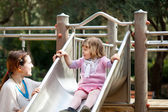 Happy mother with girl on slide — Stock Photo