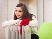 Woman warms near warm heater — Stock Photo