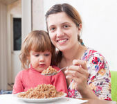 Happy woman with child eats buckwheat — Stock Photo