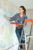 Girl paints wall with brush — Stock Photo