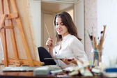 Girl paints on canvas with oil colors — Stock Photo