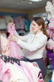 Woman chooses dress for daughter — Stock Photo