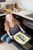 Happy woman cooking raw fish in oven — Stock Photo