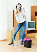 Cheerful woman in headphones washing floor with mop — Stock Photo