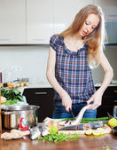 Long-haired housewife cooking saltwater fish — Stock Photo