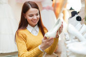 Bride choosing white shoes in shop — Stock Photo