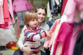 Mother with baby chooses wear at clothes shop — Stock Photo