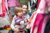 Madre con bebé elige ropa en tienda de ropa — Foto de Stock