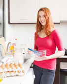 Smiling woman with whisk in home kitchen — Stock Photo