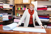 Salesclerk measures the fabric — Stock Photo