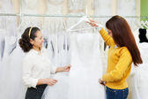 Women chooses white gown — Stock Photo
