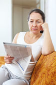 Wistful mature woman looks newspaper — Stock Photo