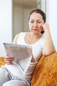 Wistful mature woman looks newspaper — Stock Photo