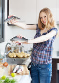 Smiling blonde woman with seabass fish — Stock Photo