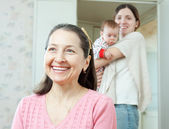 Portrait of happy woman against mother with baby — Stock Photo