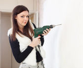 Woman drill hole in the wall — Stock Photo