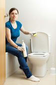 Woman cleaning toilet bowl with sponge — Stock Photo