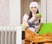 Woman relaxing near oil heater — Stock Photo