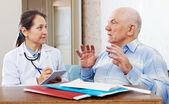 高级的病的人与成熟的医生会谈 — 图库照片