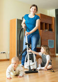 Happy mother wth two children cleans at home — Stock Photo