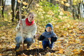 Woman and boy planting tree in autumn — Stock Photo