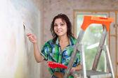 Mujer feliz pinturas pared — Foto de Stock