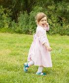 Girl in dress in green grass meadow — Stock Photo