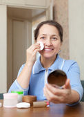 Mature woman removes makeup — Stock Photo