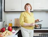 Sorridente mulher madura na cozinha doméstica — Fotografia Stock