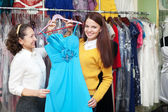 Happy women chooses blue dress — Stock Photo