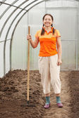 Gardener with rake in greenhouse — Stock Photo