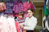Mother with girl at clothes store. Focus on woman — Stock Photo