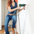 Beautiful woman in overalls with drill — Stock Photo