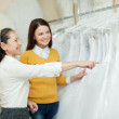 Shop assistant helps the bride in choosing bridal dress — Stock Photo