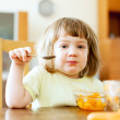 Child eats carrot salad with spoon — Stock Photo #28693255