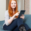 Girl with e-book on sofa — Stock Photo