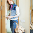 Woman with luggage loocking door — Stock Photo