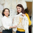 Consultant helps to girl chooses  bridal clothes — Zdjęcie stockowe