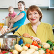 Stock Photo: Mature womcooking veggie lunch in kitchen