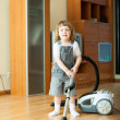Girl with vacuum cleaner on parquet — Stock Photo