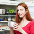 Woman with small pan near opened refrigerator — Stock Photo #28693737