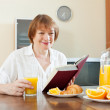 Mature woman with book during breakfast — Stock Photo #28693805