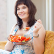 Stock Photo: Positive womeats veggie salad on sofa