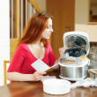 Постер, плакат: Woman unpacking and reading manual for new crockpot