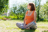 Pregnant woman sits on grass — Stockfoto
