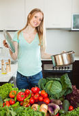 Woman cooking with pan and heap of vegetables — Stock Photo