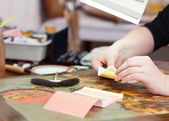 Art restorer gilding on the ancient icon — Stock Photo