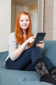 Girl with e-book on sofa — Stock Photo