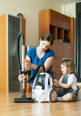 Woman teaches child to use the vacuum cleaner — Stock Photo